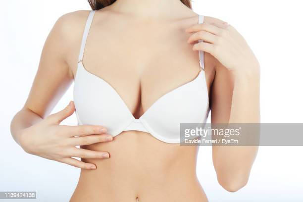 midsection of sensuous woman touching bra against white background - bras stock pictures, royalty-free photos & images