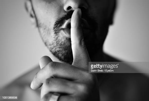 midsection of shirtless man with finger on lips - silence photos et images de collection