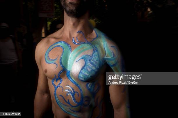 midsection of shirtless man with painted body at home - andrea rizzi foto e immagini stock