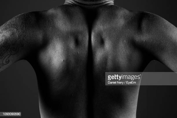 Midsection Of Shirtless Muscular Man Against Black Background