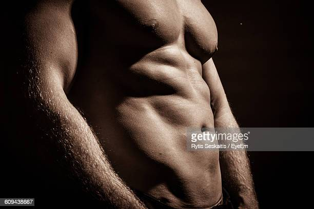 Midsection Of Shirtless Muscular Man Standing Against Black Background