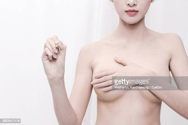 midsection of shirtless young woman covering breasts against white background - mani su seno foto e immagini stock