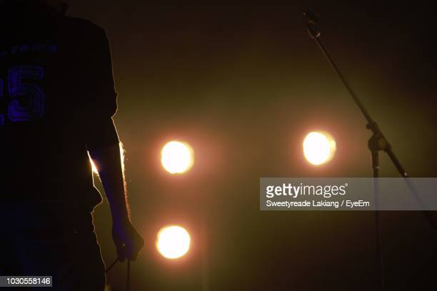 midsection of silhouette male singer standing on stage during concert - microphone stand stock photos and pictures