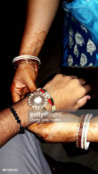 Midsection Of Sister Tying Rakhi In Brother Hand