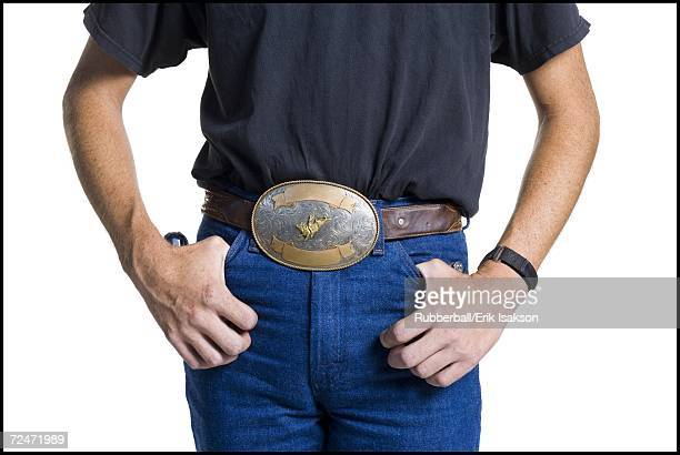 Midsection of slender young man wearing a big belt buckle