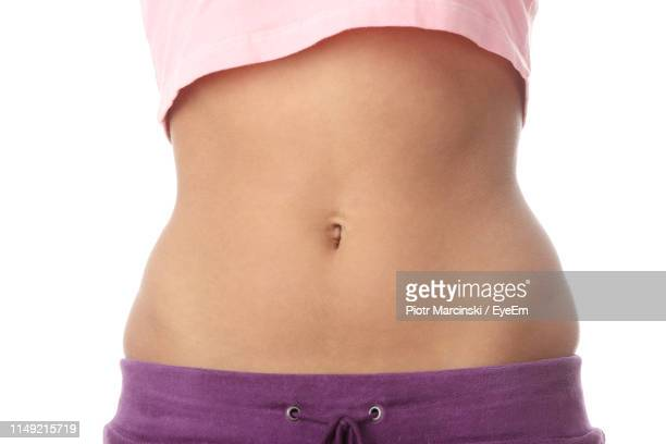 midsection of slim woman standing against white background - belly stock pictures, royalty-free photos & images