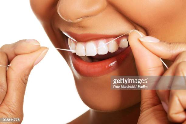 Midsection Of Smiling Woman Flossing Her Teeth Against White Background