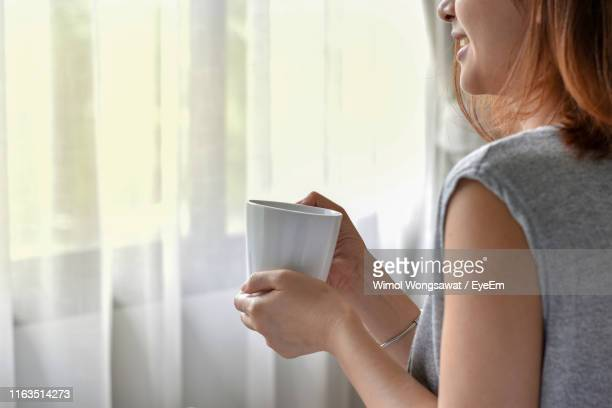 midsection of smiling woman holding coffee mug against curtain - wimol wongsawat stock photos and pictures