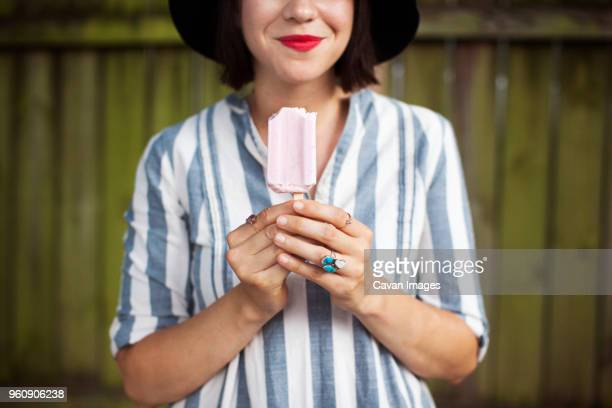 Midsection of smiling woman holding popsicle