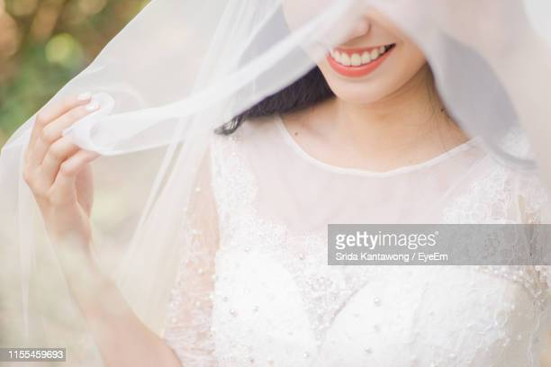 midsection of smiling woman in wedding dress standing outdoors - veil stock pictures, royalty-free photos & images
