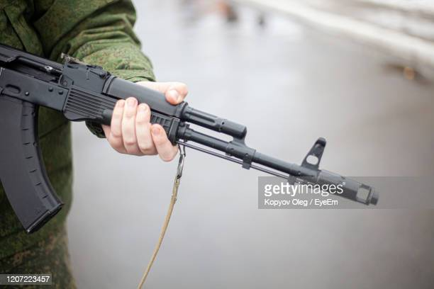 midsection of soldier holding gun - kalashnikov stock pictures, royalty-free photos & images