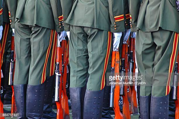 Midsection Of Soldiers Standing Side By Side
