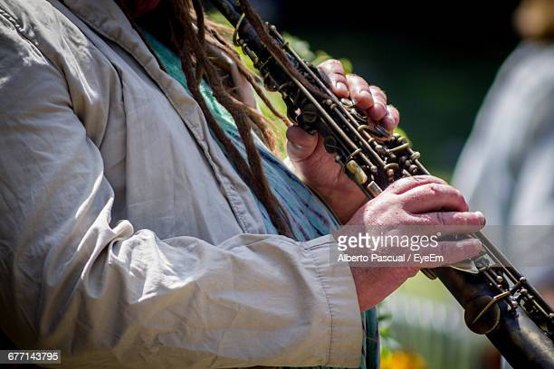 midsection of street musician playing oboe - oboe stock-fotos und bilder