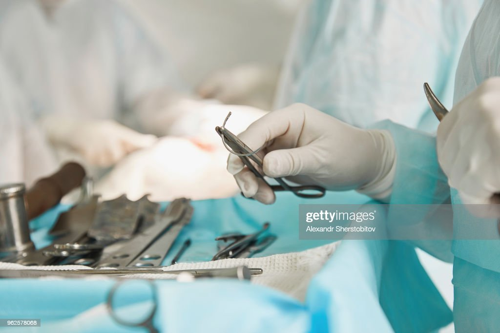 Midsection of surgeon holding surgical scissors during surgery at hospital : Stock Photo