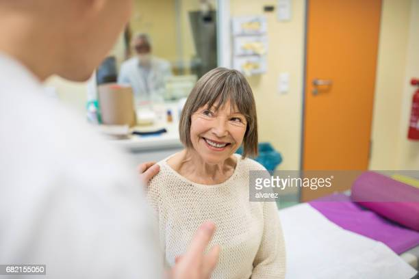 Midsection of surgeon talking with senior woman