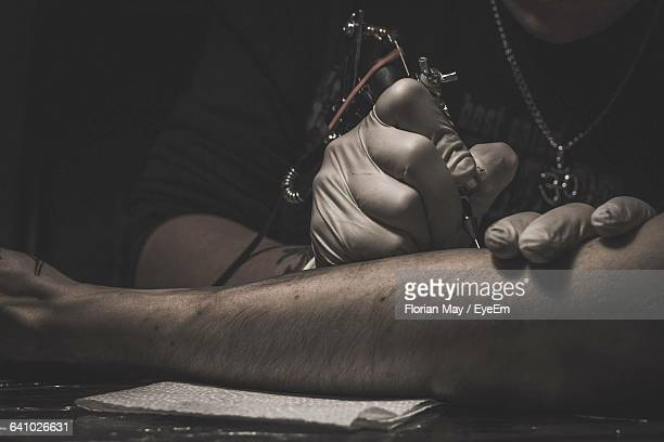Midsection Of Tattoo Artist Working On Customer Leg