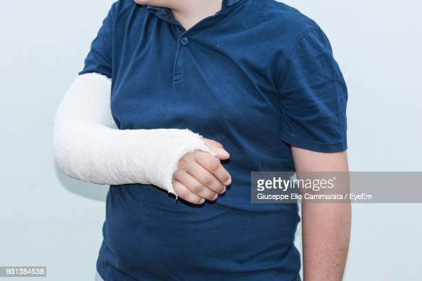 Midsection Of Teenage Boy With Injured Hand Against White Background