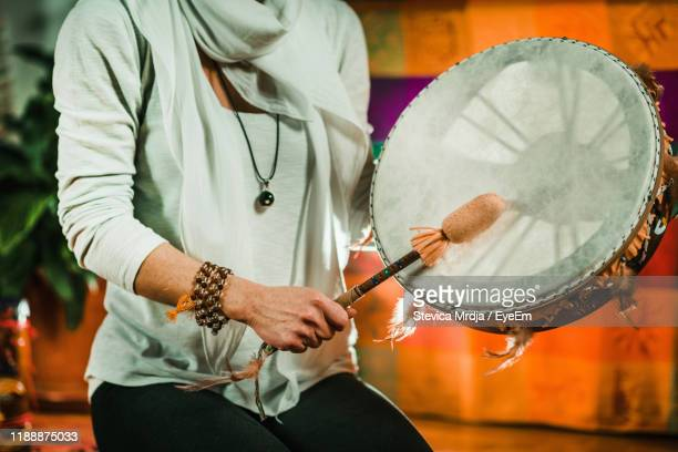 midsection of therapist playing drum while performing music therapy at spa - spirituality stock pictures, royalty-free photos & images