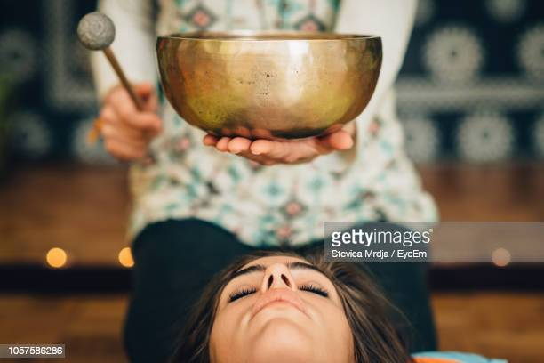 midsection of therapist playing rin gong by young woman at spa - gong stock pictures, royalty-free photos & images