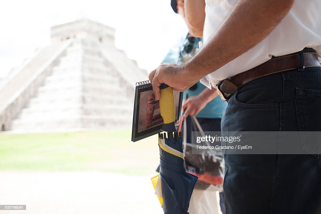 Midsection Of Tourist Holding Umbrella And Book Against Mayan Pyramid : Foto stock