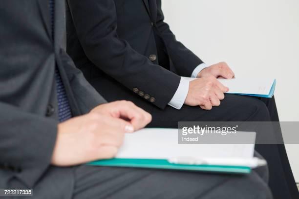 Midsection of two businessmen sitting on chair