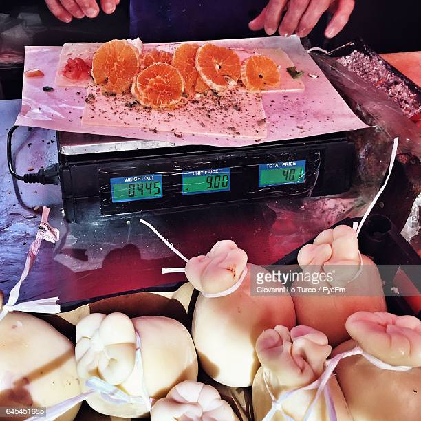 Midsection Of Vendor Measuring Sliced Fish On Weight Scale In Market