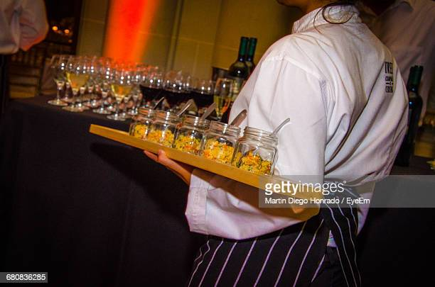 Midsection Of Waiter Holding Glass Jars