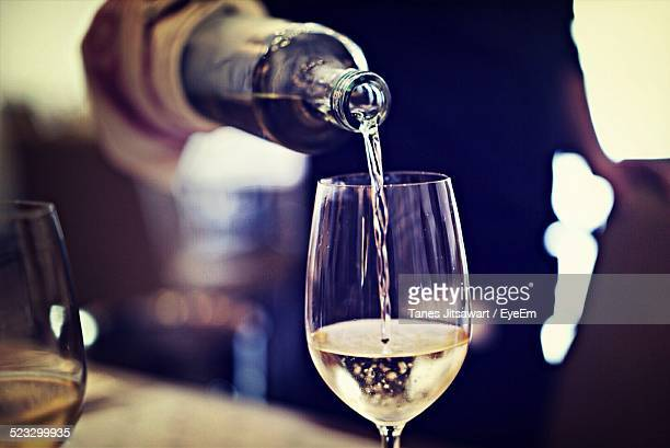 midsection of waiter pouring wine in glass at restaurant - transbordar imagens e fotografias de stock