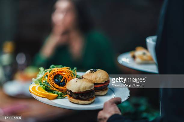 midsection of waiter serving food to woman in restaurant - serving food and drinks stock pictures, royalty-free photos & images