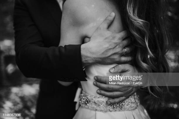 midsection of wedding couple embracing while standing outdoors - marriage stock pictures, royalty-free photos & images