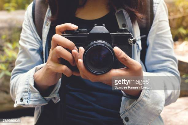midsection of woman adjusting camera lens outdoors - mid section stock pictures, royalty-free photos & images