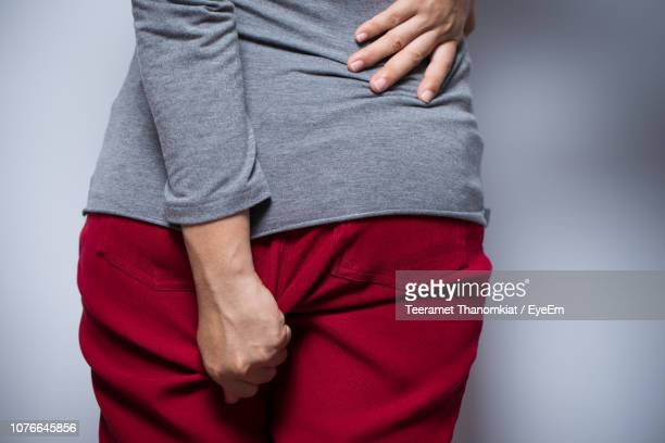 midsection of woman adjusting pants while standing over gray background - uncomfortable stock pictures, royalty-free photos & images