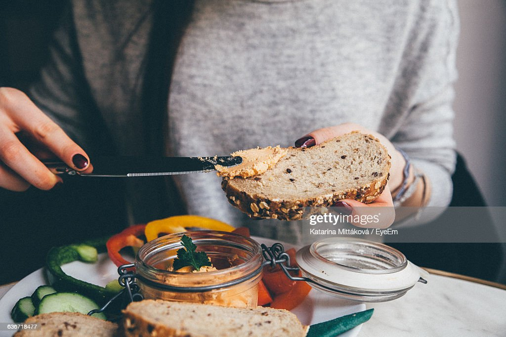 Midsection Of Woman Applying Spread On Bread At Home : Stock Photo
