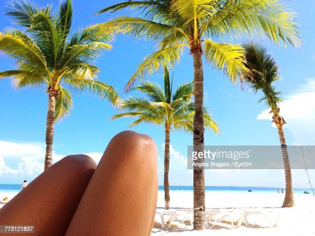 Midsection Of Woman At Beach Against Blue Sky