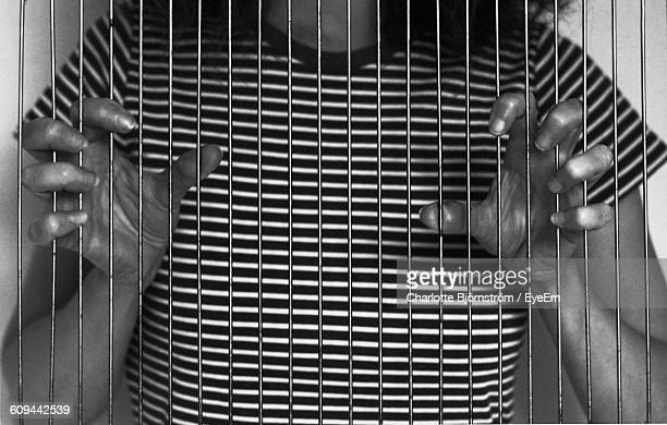 midsection of woman behind prison bar - prison escape stock pictures, royalty-free photos & images