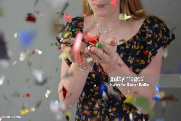 Midsection Of Woman Blowing Confetti Against Gray Background