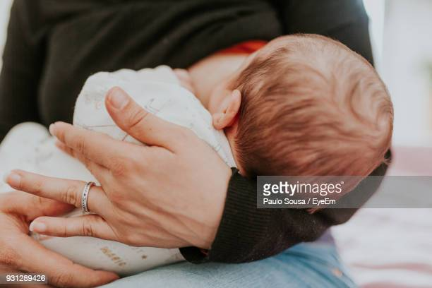 Midsection Of Woman Breastfeeding Baby