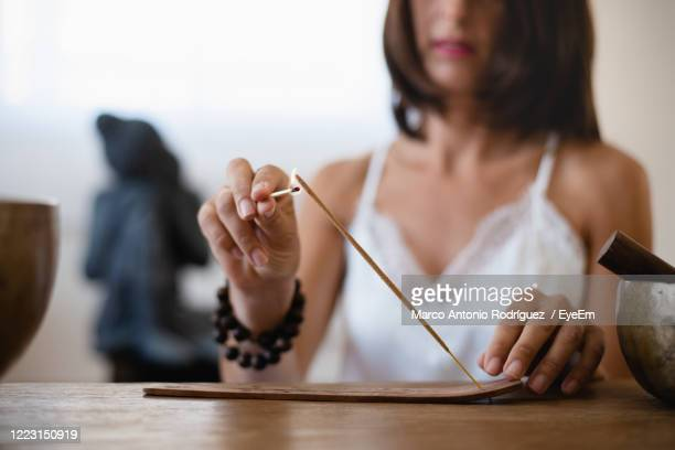 midsection of woman burning incense on table - incense stock pictures, royalty-free photos & images