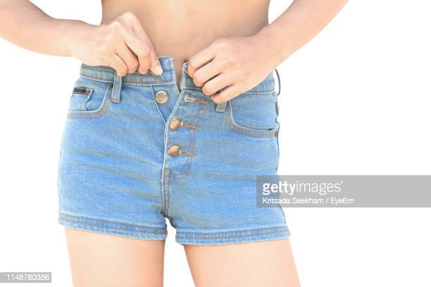 midsection of woman buttoning hot pants against white background - hands in her pants stock pictures, royalty-free photos & images