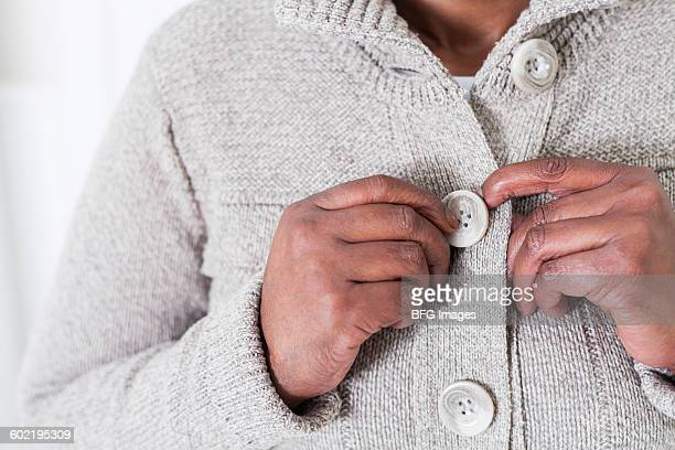 Mid-section of woman buttoning sweater, Cape Town, South Africa