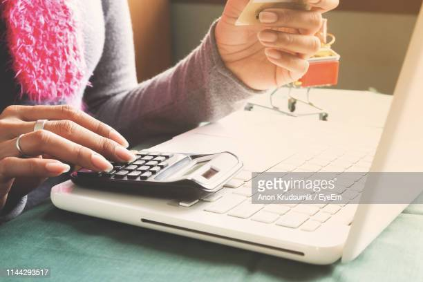 Midsection Of Woman Calculating While Shopping Online