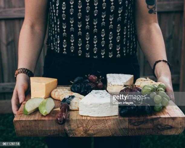 midsection of woman carrying breakfast on wooden board - kaasplank stockfoto's en -beelden