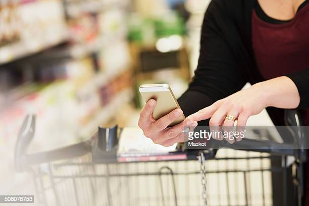 Midsection of woman checking shopping list in supermarket
