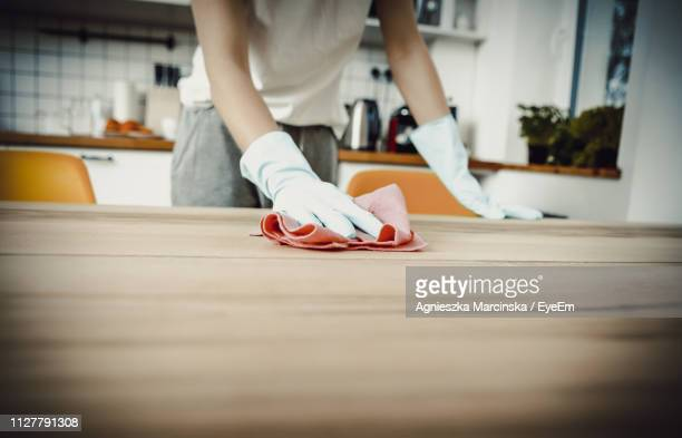 midsection of woman cleaning wooden table at home - washing up glove stock pictures, royalty-free photos & images