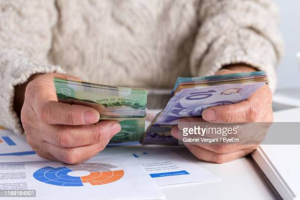 midsection of woman counting money on table - canadian currency stock pictures, royalty-free photos & images