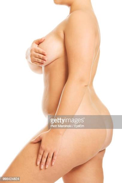 Midsection Of Woman Covering Breast With Hands Against White Background