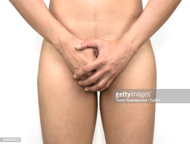 midsection of woman covering vagina while standing against white background - vrouwelijk geslachtsorgaan stockfoto's en -beelden