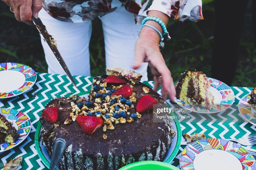 Midsection Of Woman Cutting Birthday Cake On Table Stock Foto