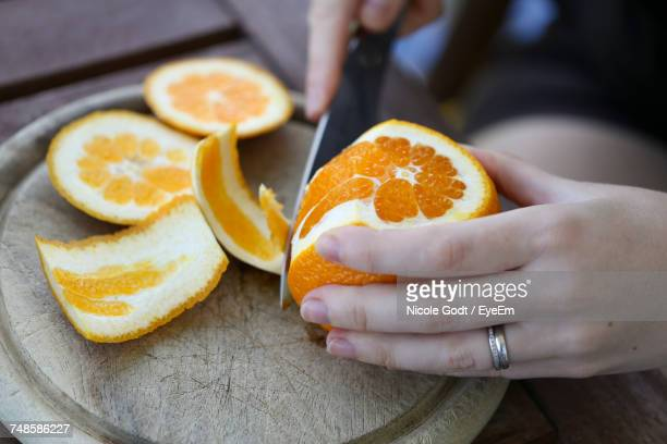 Midsection Of Woman Cutting Fruit