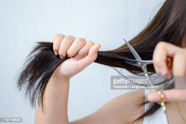 midsection of woman cutting hair against white background - cutting stock pictures, royalty-free photos & images